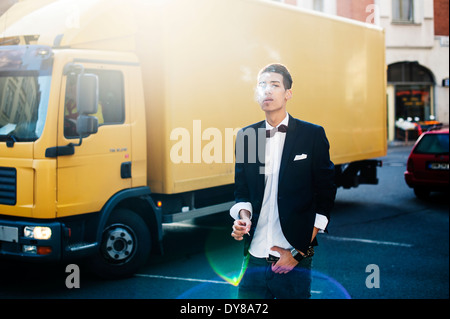 Smoking young man in the city - Stock Photo