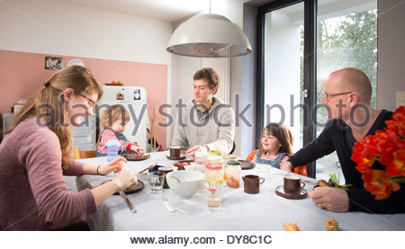 Young family having breakfast with their grandfather - Stock Photo