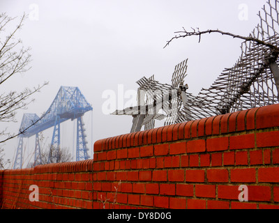 Historic Transporter Bridge spanning the River Tees, behind brick wall at Middlehaven, Middlesbrough, Teesside, - Stock Photo