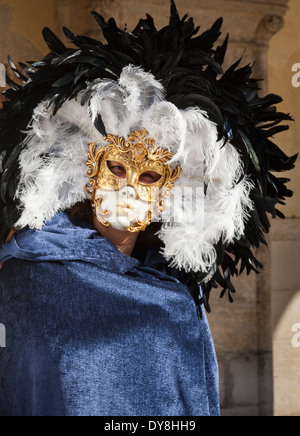 Close up of man in historic gold mask and feathered headgear at the carnival in Venice - Stock Photo