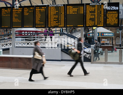 Blurred people hurrying to catch train below destination boards Newcastle upon Tyne station north east England UK - Stock Photo