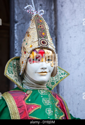 Close up of masked jester in bright costume during the Venice carnival - Stock Photo