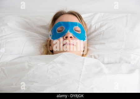 Young woman has a hangover, his eyes cooled with a cooling mask - Stock Photo