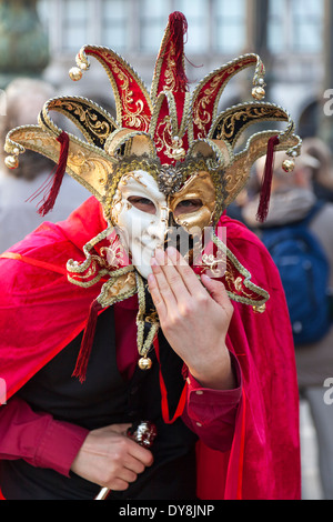 Costumed jester with mask smiles at camera during the Venice carnival - Stock Photo