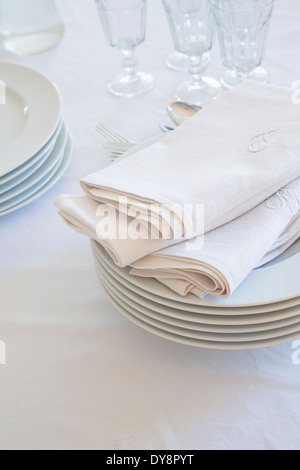 Glasses, stack of plates and cloth napkins on white table cloth - Stock Photo