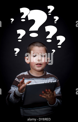 Boy with question mark symbols around his head using tablet - Stock Photo