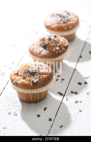 Row of three muffins in paper cups sprinkled with powdered sugar and chocolate shavings on white wooden table - Stock Photo