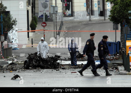 Athens, Greece. 10th Apr, 2014. Police bomb disposal experts search for evidence next to remains of a car after - Stock Photo