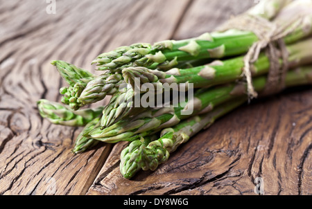 Bunch of asparagus on a wooden table. - Stock Photo