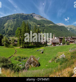 Mountain village church town village field meadow trees summer mountains hills Evolene Val d'Herens Wallis Valais - Stock Photo