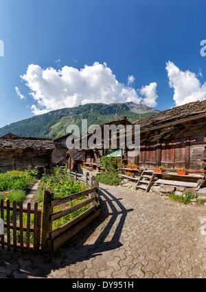 Ancient wooden chalet farmhouses town village summer mountains hills Evolene Val d'Herens Wallis Valais Switzerland - Stock Photo