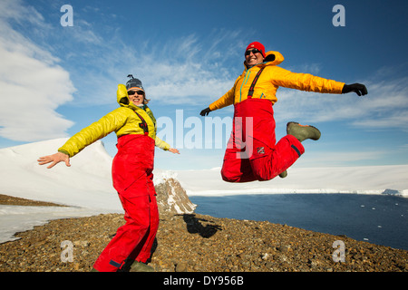 A man and woman jumping for joy from an expedition cruise on Joinville Island just off the Antarctic Peninsular. - Stock Photo