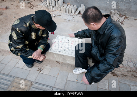 Two friends playing Xiangqi also called Chinese chess on the street in Beijing, China - Stock Photo