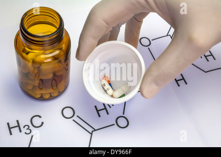 Chemistry science formula and tablets, Hand with white latex glove holds a plastic cup with several pills