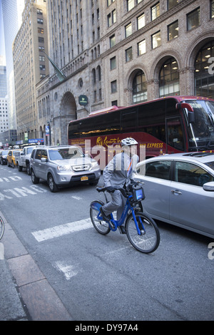 Man rides a Citi Bike to beat the traffic on 42nd St in midtown Manhattan one of the most congested urban centers - Stock Photo