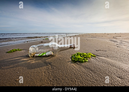 Message in a glass bottle with a cork in the top washed up on a beach - Stock Photo