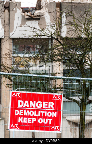 Danger Demolition Keep Out sign attached to a fence surrounding a building site where an old building is being demolished - Stock Photo