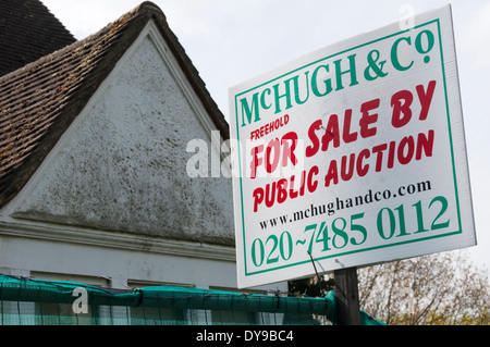 A For Sale By Public Auction sign on a single unoccupied house in south London. - Stock Photo