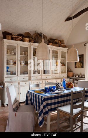 Rustic country kitchen with French style cabinets, checked blue tablecloth and woven wicker pendant lights - Stock Photo