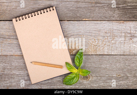 Blank notepad for copy space and basil leaves on wooden table - Stock Photo