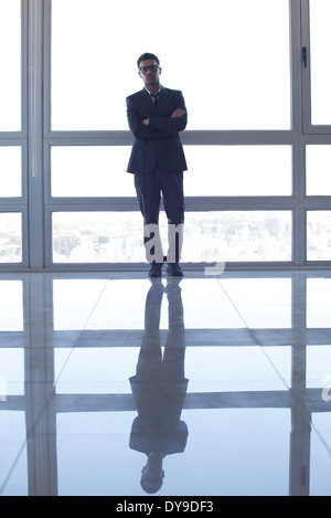 Businessman learning against high rise window, backlit by sunset glow - Stock Photo