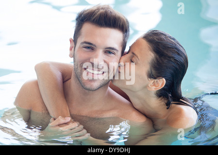 Couple relaxing together in pool, woman kissing man's cheek - Stock Photo