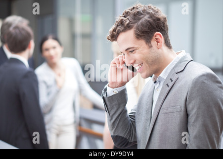 Businessman using cell phone outdoors - Stock Photo