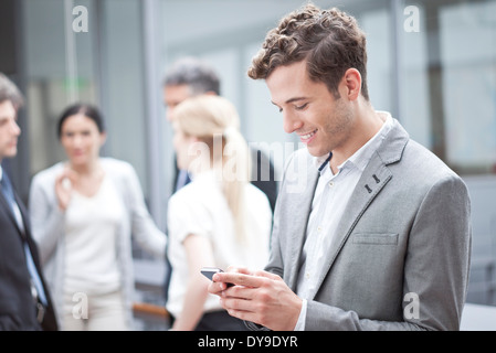 Businessman using cell phone while on the move - Stock Photo