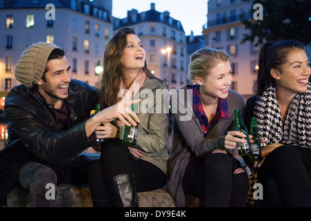 Friends having beers together outdoors - Stock Photo