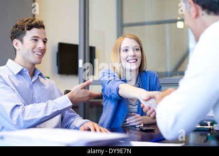 Businessman shaking hands with client in meeting - Stock Photo