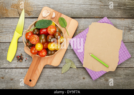 Cherry tomatoes on cutting board over wooden table background with paper for copy space - Stock Photo