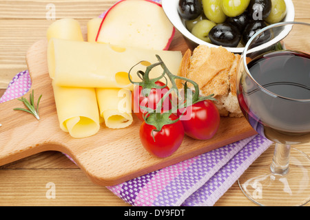 Red wine with cheese, olives, bread, vegetables and spices on wooden table - Stock Photo