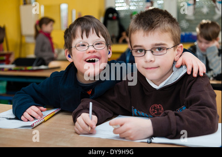 Non-disabled and disabled pupils (in this case a boy suffering from Down's syndrome) learn together in the same - Stock Photo