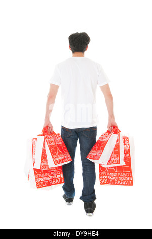 Young man is walking away by the sale with many bags - Stock Photo
