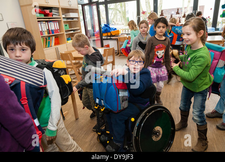 Non-disabled and disabled students (in this case a boy in a wheel chair) learn together in the same class in a primary - Stock Photo