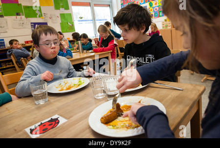 Non-disabled and disabled pupils (in this case a boy suffering from Down's syndrome) have lunch together in their - Stock Photo