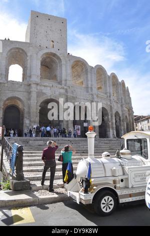 Le petit train tourist vehicle pauses at the Roman Amphitheatre in Arles France - Stock Photo