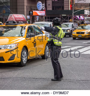 New York Police Department (NYPD) directing traffic in Manhattan, New York City, with a yellow taxi cab - Stock Photo