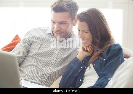 Couple relaxing at home looking at laptop computer together - Stock Photo