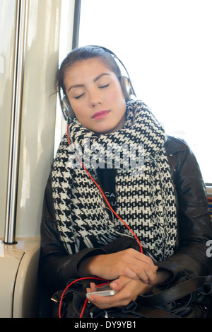 Young woman listening to music on subway train with eyes closed - Stock Photo