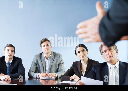 Business associates listen as colleague makes presentation during meeting - Stock Photo