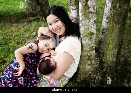 Mother with baby and little girl outdoors - Stock Photo