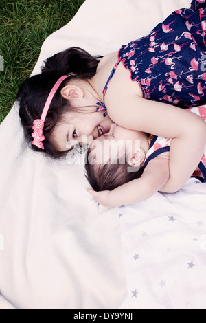 Little girl with baby brother lying on blanket outdoors - Stock Photo