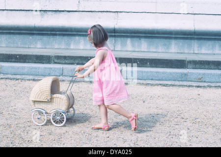 Little girl pushing miniature baby carriage - Stock Photo
