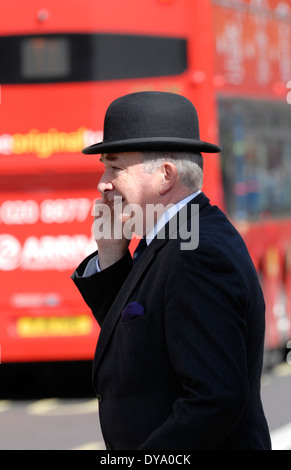 London, England, UK. City gent in a bowler hat on mobile phone in the street - Stock Photo