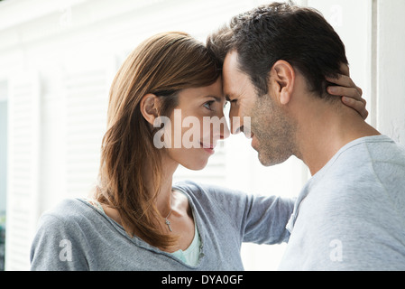 Couple touching noses by window - Stock Photo