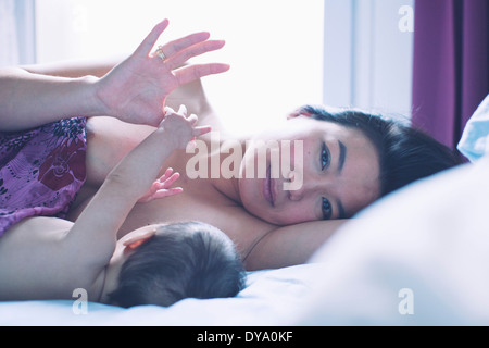 Mother lying on bed with baby, portrait - Stock Photo