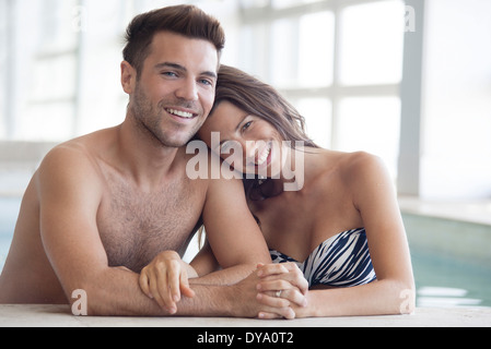 Young couple in pool together, portrait - Stock Photo