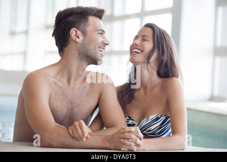 Couple relaxing together in indoor swimming pool - Stock Photo