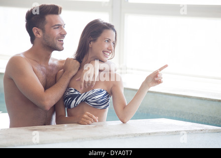 Couple wading in indoor pool looking at view through window - Stock Photo